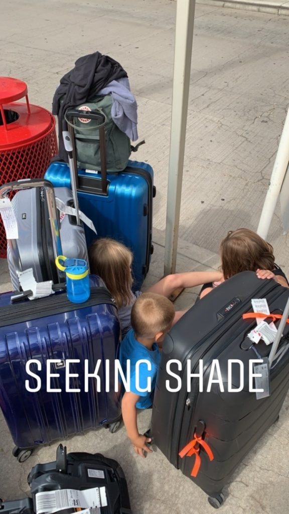 Kids seeking shade outside van rental building