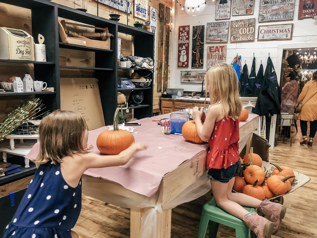 Girls painting pumpkins in craft area at shop