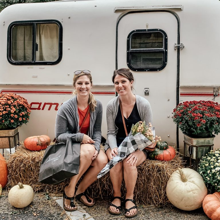Sara and Katie seated on hay bales with fall mums and pumpkins in front of vintage camper